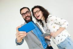 Coppie dei pantaloni a vita bassa in vetri che fanno selfie isolato sul bianco Immagini Stock