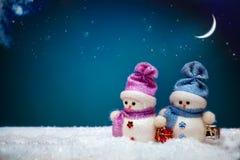 Coppie dei pupazzi di neve sul fondo blu di inverno Fotografie Stock Libere da Diritti