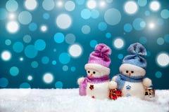 Coppie dei pupazzi di neve sul fondo blu di inverno Immagini Stock