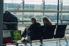 Coppie dei turisti che aspettano nel corridoio di imbarco con una valigia all'aeroporto Fotografia Stock Libera da Diritti