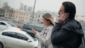 Coppie dei turisti che camminano in una via della città con le applicazioni di navigazione di uso del telefono, l'uomo e la passe archivi video