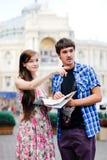Coppie dei turisti che osservano sul programma nel centro urbano Fotografia Stock Libera da Diritti