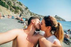 Coppie dei viaggiatori che prendono i selfies e che baciano sulla spiaggia sul fondo del mare Immagini Stock Libere da Diritti