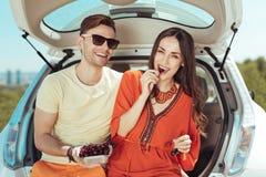 Coppie dei viaggiatori che si siedono nel tronco della loro automobile che mangia le ciliegie immagini stock libere da diritti