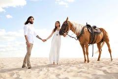 Coppie dei viaggiatori che si tengono per mano, camminanti attraverso il deserto sul cavallo Fotografie Stock