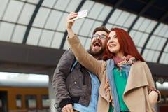 Coppie dei viaggiatori dei pantaloni a vita bassa che fotografano un selfie con uno smartphone in una stazione ferroviaria concet Fotografia Stock
