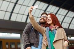 Coppie dei viaggiatori dei pantaloni a vita bassa che fotografano un selfie con uno smartphone in una stazione ferroviaria concet Fotografie Stock Libere da Diritti