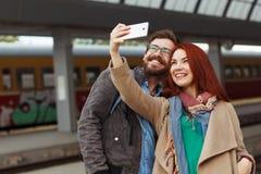 Coppie dei viaggiatori dei pantaloni a vita bassa che fotografano un selfie con uno smartphone in una stazione ferroviaria concet Immagini Stock Libere da Diritti