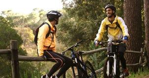 Coppie del ciclista in mountain-bike che prendono una rottura mentre ciclismo video d archivio