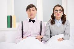 Coppie del nerd. Coppie sorprese del nerd che si siedono sul letto e sul lookin immagine stock