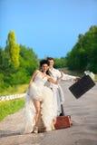 Coppie del Newlywed che fanno auto-stop su una strada Fotografie Stock Libere da Diritti