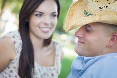 Coppie del paese della corsa mista con il cowboy Hat Flirting in parco fotografia stock