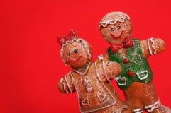 Coppie del pan di zenzero sopra fondo rosso Biscotti di natale Fotografie Stock