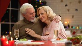 Coppie del pensionato che abbracciano e che guardano alla macchina fotografica, ritratto felice della famiglia la vigilia di nata stock footage