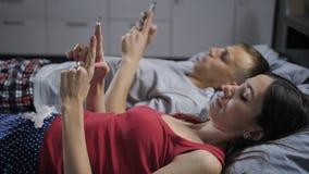 Coppie del primo piano a letto facendo uso dei cellulari stock footage