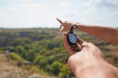 Coppie del viaggiatore che cercano direzione con una bussola in montagne di estate Ricerca del modo sul canyon fotografia stock
