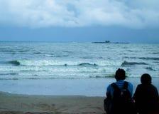 Coppie del viaggiatore che si siedono insieme su una spiaggia Fotografie Stock Libere da Diritti