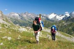 Coppie del viaggiatore con zaino e sacco a pelo in montagne Fotografia Stock Libera da Diritti
