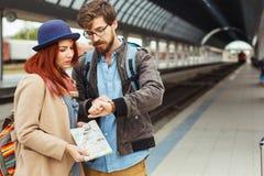 Coppie del viaggiatore dei pantaloni a vita bassa che esaminano orologio astuto mentre aspettando il treno alla stazione ferrovia Immagine Stock