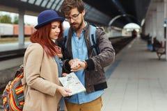 Coppie del viaggiatore dei pantaloni a vita bassa che esaminano orologio astuto mentre aspettando il treno alla stazione ferrovia Fotografie Stock