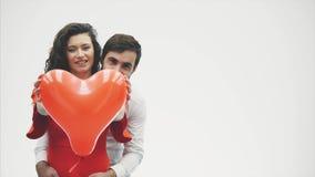 Coppie delicate la bellezza della ragazza e del suo tipo bello, tenendo il cuore sotto forma di palloni e di baci felice stock footage