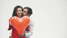 Coppie delicate la bellezza della ragazza e del suo tipo bello, tenendo il cuore sotto forma di palloni e di baci felice archivi video