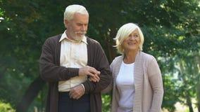 Coppie dell'anziano che abbracciano e che camminano al parco di estate, godente insieme del passatempo video d archivio