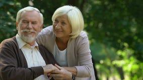 Coppie dell'anziano che abbracciano e che guardano felicemente sui loro nipoti che giocano nel parco archivi video