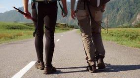 Coppie dell'autostoppista di viaggio su una strada archivi video