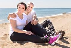 Coppie dell'uomo anziano con una donna in camice bianche che si siedono sulla sabbia sulla spiaggia immagini stock libere da diritti