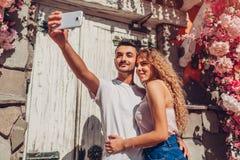 Coppie della corsa mista nell'amore che prende selfie sullo smartphone che cammina nella città Uomo e donna bianca arabi felici a fotografie stock libere da diritti