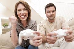 Coppie della donna dell'uomo che giocano il video gioco della sezione comandi Immagine Stock