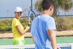Coppie della donna dell'uomo che giocano a tennis avendo lezione Immagini Stock Libere da Diritti