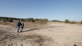Coppie della fucilazione che wolking sulla sabbia archivi video