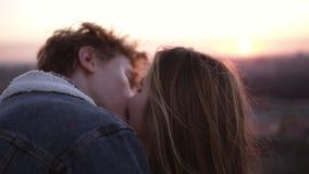 Coppie della gioventù che godono di un bacio romantico mentre stando sull'alto tetto ventoso con un fondo urbano Vista di paesagg archivi video