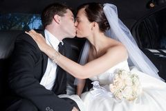 Coppie della persona appena sposata che baciano in limousine Fotografie Stock