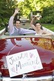 Coppie della persona appena sposata che ondeggiano in automobile convertibile Fotografie Stock Libere da Diritti