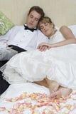 Coppie della persona appena sposata che si rilassano a letto fotografia stock