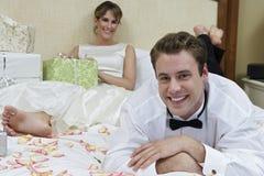 Coppie della persona appena sposata che si rilassano a letto immagini stock