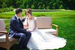 Coppie della persona appena sposata che si siedono sul sofà immagine stock libera da diritti