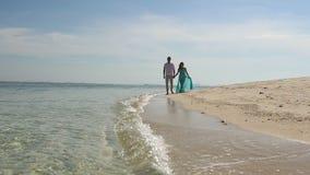 Coppie della ragazza e di Guy Walk Barefoot biondi lungo il bordo di acqua video d archivio