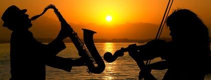 Coppie della siluetta che giocano jazz Immagini Stock