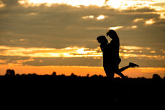Coppie della siluetta nell'amore sul fondo del sole Immagini Stock Libere da Diritti