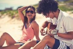 Coppie della spiaggia della chitarra Immagine Stock