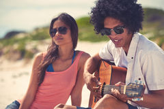 Coppie della spiaggia della chitarra Immagini Stock
