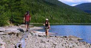 Coppie della viandante che fanno un'escursione vicino alla riva del fiume 4k video d archivio