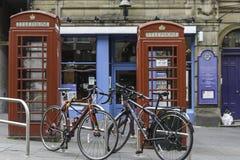 Coppie delle bici davanti a due cabine telefoniche rosse in una via di Edimburgo del centro Immagini Stock