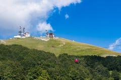 Coppie delle cabine di funivia che scalano montagna fotografia stock