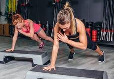 Coppie delle donne che si preparano sopra gli steppers in aerobico Immagine Stock