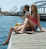 Coppie delle ragazze degli amici che si siedono vicino al ponte Fotografia Stock Libera da Diritti